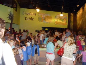 This room, which smells heavily of chlorine, has a big wrap-around table filled with water and sand. Kids can build dams and create rivers and streams, complete with plastic dinosaurs and palm trees. I suppose on a slower day they could watch as the water washed away their dams and moved the dinosaurs and trees around, but it was packed when we went. See that crowd? Bleh.