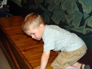 Brandon got tired of playing and decided to climb on the benches instead.